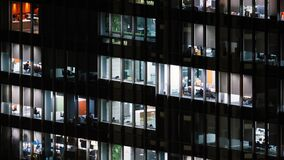 Time lapse of people working late night, office windows view on business center building facade
