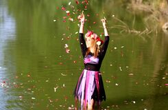 Time Lapse Photo of Woman Standing in Green Body of Water While Pouring Flower Petals on Air during Daytime Royalty Free Stock Photography