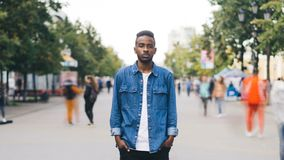 Time-lapse portrait of African American man in casual clothes looking at camera standing in busy street downtown. Time-lapse portrait of African American young stock footage