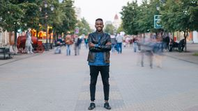 Time-lapse portrait of cheerful African American man standing in city center wearing stylish clothes looking at camera