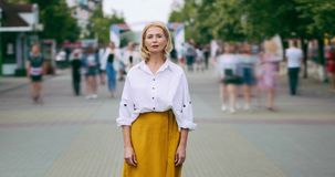 Time lapse portrait of good-looking mature woman in elegant clothing in street. Standing alone looking at camera with serious face. People, life and summer stock footage