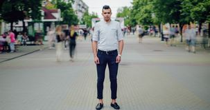 Time lapse portrait of handsome Arabian man in casual clothing outdoors in city. Street standing alone with serious face looking at camera while people moving stock footage