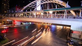Time-lapse of public sky walk and traffic at Chong Nonsi sky train station at night, Bangkok, Thailand. 4k Time-lapse of public sky walk and traffic at Chong stock video footage