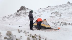 Time lapse of put up tent in winter mountains stock video