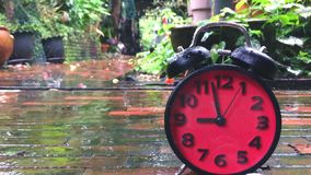 Time lapse of a red alarm Clock speeding up on rainy stock footage