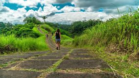 Time-lapse of running clouds and people walking along the trail of the artist in Ubud on the island of Bali in Indonesia stock video footage