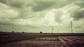 Rural landscape with dark clouds. Time lapse of rural landscape with fields and wind turbines ans some dark cumulonimbus clouds gathering over sky stock video