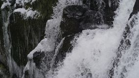 Time lapse of rushing waterfall cascading down icy rocks stock footage
