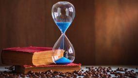 Time lapse sand clock on the old book and coffee seed on wooden table. Copy space for text. The concept of time to read books stock footage
