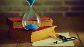Time lapse sand clock with old books and pen with old paper on the wooden table. Concept of travel planning stock video
