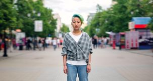 Time lapse of serious Asian lady hipster standing in street in flow of people. Time lapse portrait of serious Asian lady hipster standing in city street in flow stock footage