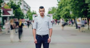 Time lapse of serious mixed race man standing alone in pedestrian street in city stock footage