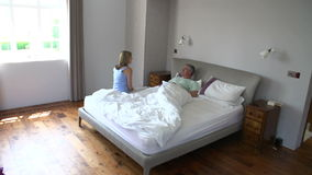 Time Lapse Shot Of Couple Getting Up And Ready In Bedroom Stock Photo