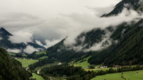 Alpine rain weather time lapse. Time lapse shot of fog and rain clouds gathering in the valley of Kals am Grossglockner in the Austrian Hohe Tauern region before stock video footage