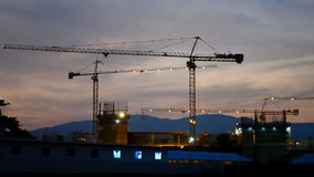 Time lapse silhouette crane building and dusk time Stock Image
