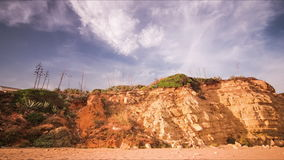 Time lapse sky above rocky cliff on sandy beach. Running clouds in blue sky stock video