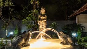 Time lapse small magic garden fountain. Night scene. The water comes from the jug in woman hands, frogs. Asian fountain stock video footage