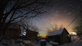 Time lapse of the starry sky in the winter garden. With buildings and trees stock video
