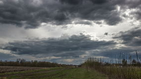 Time lapse storm clouds moving over the field. Spring landscape footage stock video