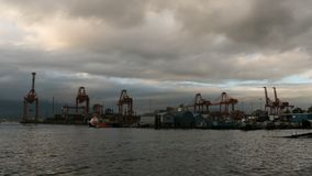 Time lapse of stormy clouds over Port of Vancouver BC from daylight into evening stock footage