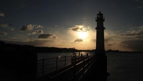 Time lapse of the sun going down behind a lighthouse stock video footage