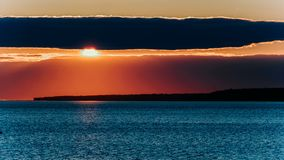 Time-lapse sun sets behind a cloud - a red-pink sunset on the sea or a large lake stock video