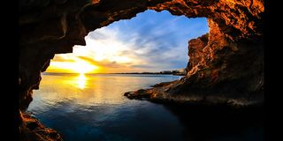 Time Lapse Sunset through a Cave Cyprus (4K). A Time Lapse Sunset seen through a Cave in Ayia Napa Cyprus on the Mediterranean Sea. The Sun is just setting
