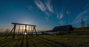 Time-lapse of sunset by a lakeside. Campsite and playground stock video footage