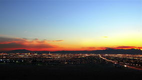 Time lapse sunset over distant city skyline stock video footage