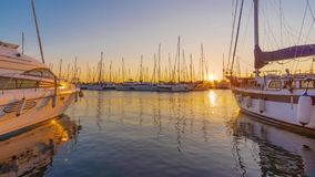 Time Lapse. Sunset scene at marina with yachts tied to the docks, sun and sky beautiful color reflected in still water. stock video footage