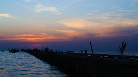 Time lapse of sunset at sea with silhouette of jetty stock video footage