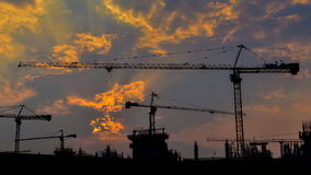 Time lapse sunset and silhouette crane working in big construction site (zoom in) stock video