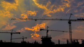 Time lapse sunset and silhouette crane working in big construction site (zoom out)