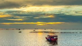 Time lapse of sunset sky at sea with boat mooring foreground stock video