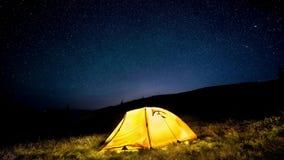 time lapse Tienda de campaña que brilla intensamente en el bosque de la montaña de la noche debajo de un cielo estrellado almacen de metraje de vídeo