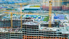 Time lapse tilt shift builders and cranes working on the construction site.  Stock Photo