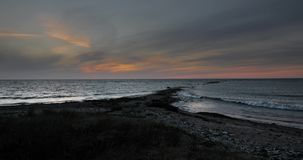 Time lapse of twilight over the sea. Time lapse of twilight over the Baltic Sea on a stone covered beach with tall grass stock footage