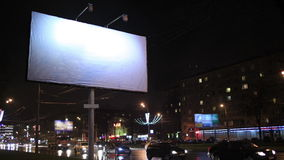 Time lapse of urban scene with an empty billboard, by night. Time lapse of urban scene with an illuminated empty billboard on the side of a street with cars in stock footage