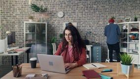 Time lapse van meisje het werken met laptop in creatief bureau terwijl zich medewerkers het bewegen stock videobeelden