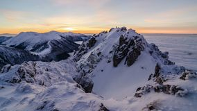 Colorful golden sunset in snowy mountains in winter above mist clouds. Dolly shot time lapse day to night. Time lapse video of beautiful sunset over winter snowy stock video footage