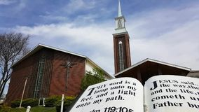 Time lapse of clouds passing over church. A time lapse video of clouds passing over a church as camera pans to large Bible verse stock video