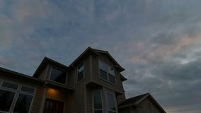 Time lapse video of clouds and sunset with window glass reflection over house 4k stock video footage