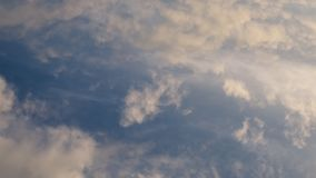 Time lapse video of white cumulus and fleecy clouds morphing on blue sky, 4K stock video
