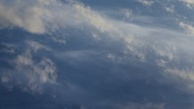 Time lapse video of white cumulus and fleecy clouds morphing on blue sky, 4K stock footage