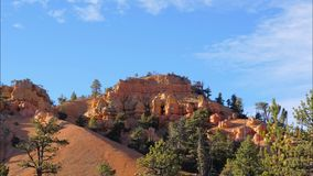 A Time Lapse Of The Bryce Canyon Rock And Clouds Above. Time lapse view of the Bryce Canyon rocks with pine trees and bushes, above which small slight clouds are stock footage