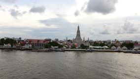 Time lapse of Wat Arun temple or with moving clouds and sun rays, water transport of Chao Phraya River.  stock video