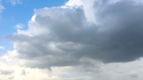 Time-lapse of the rain cloud moving and transforming with the blue sky. Time-lapse of the white and rain cloud moving and transforming with the blue sky on the stock video