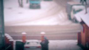 Time lapse of a wintry urban landscape. Time lapse of a wintry landscape with snow falling on blurred city road background with cars driving by and people stock video
