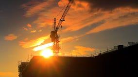 Time Lapsevideo met een silhouet van een kraan die bij een bouwwerf aan gouden zonsondergang met blauwe hemel, wolken werken en stock videobeelden