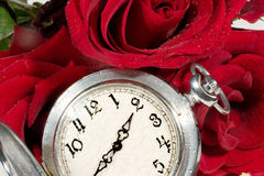 Time of love. Antique pocket watch on red rose buds and petals Royalty Free Stock Images